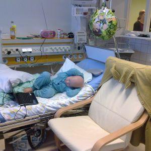 Cancersjukt ban ligger i patientsäng på sjukhus och använder bärbar dator.