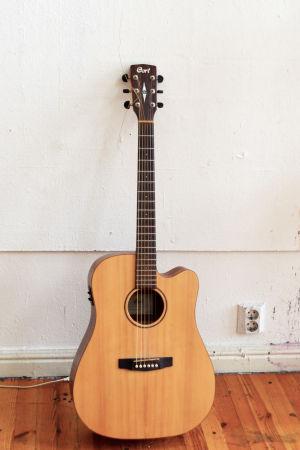 En akustiskt gitarr står lutad mot en vit vägg.