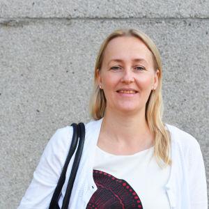 Helsinge Gymnasiums rektor Johanna Blomstedt framför grå stenvägg.