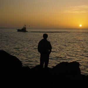 Ensam man vid klippor vid solnedång