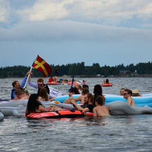 Ett gäng människor som dricker öl i olika flytetyg utanför Sandö i Vasa