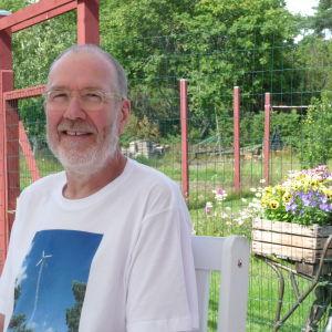 Janne Gröning sitter ute i sin trädgård i Keistiö i Iniö