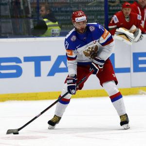 Koncentrerad ishockeyspelare med puck.