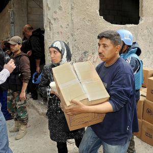 Hjälparbetare från FN distribuerar mat i Damaskus, Syrien.