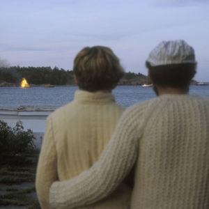 Pariskunta katsoo merellä palavaa kokkoa rannalta