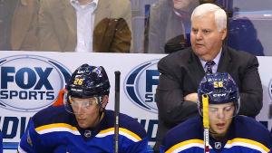 Ishockeytränare med korslagda armar bakom spelarbänken.
