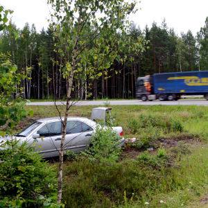 En silverfärgad bil har kört av vägen och ligger i ett dike. I bakgrunden ser man en lastbil som kör förbi.