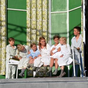 Maria sitter i sängen med barnen von Trapp. Från vänster: Simon Wadenström, Felicia Wadenström, Ellen Haakana, Sarah Nedergård, Inka Louneva, Minea Korenius och Birk Lerviks.