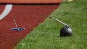 En slägga ligger på gräsmattan vid en idrottsplan.