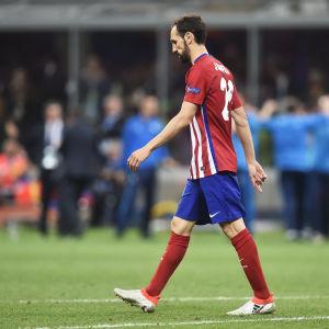 Besviken fotbollspelare vandrar längs planen.
