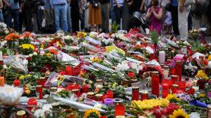 Människor sörjer och lägger blommor vid attentatsplatsen i München på söndagen 24.7.2016