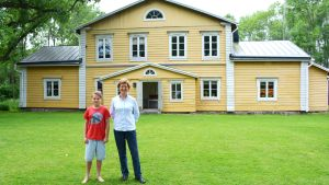 Ulla Tillander-Godenhielm och barnbarnet Filip framför Ollas gård i Pernå.