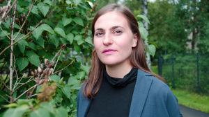 Kvinna i blå jacka står framför en grönskande buske.