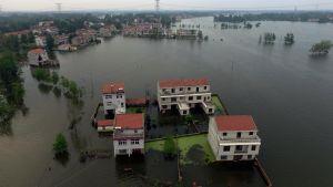 Vita hus med rött tak står i vatten från översvämning i porvinsen Hubei i Kina.