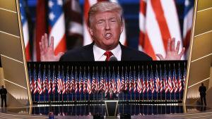 Donald Trump står bakom ett guld- och svartfärgat podium med flera amerikasnka flaggor och en enorm screen bakom honom som streamar talet den 21 juli 2016.