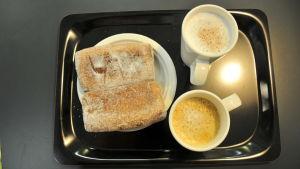 munkar och kaffekoppar på en bricka