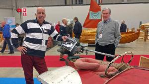 Nisse Häggblom och en annan Nisse står intill en gammal racingbåt i faner från 30-talet