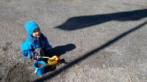 Fyraårig pojke leker med hink och lastbil i gruset.