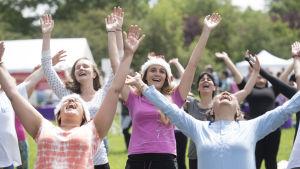 Personer skrattar med händerna i vädret.