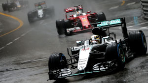 Formel 1-bilar på rad under regnig tävling.