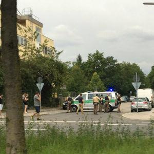 Förbipasserande vid polisbil nära köpcentret i München.