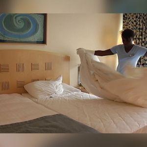 Kvinna bäddar hotellsäng