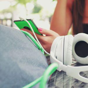 Flicka med mobiltelefon och hörlurar.