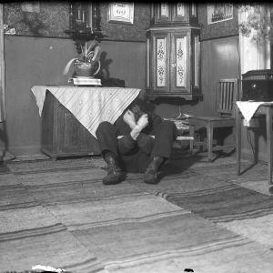 """En man leker leken """"lugg björn"""", och sitter på golvet med knäna uppåtdragna och armarna korslagda. Bilden är tagen 1938 i Närpes, Kalaks."""
