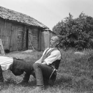 """Två män leker leken """"resa mast"""", där den ena ska försöka resa sig från liggande ställning i den andras famn utan att ta stöd av sina armar. Bilden är tagen 1929 i Strömfors, Kungsböle."""