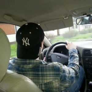 Ung man kör bil.