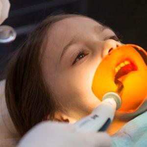 En flicka ligger i tandläkarstolen med tandläkarinstrument i munnen.