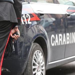 En italiens carabinieripolis håller i ett vapen bakom en polisbil.