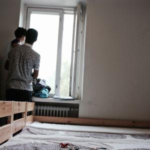 Pappa står med sin son vid ett fönster.