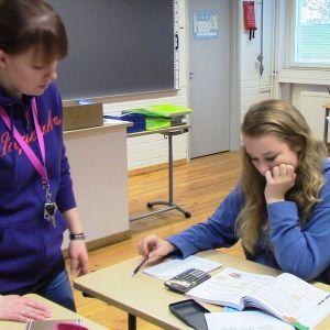Opettaja ohjaa matematiikan tunnilla