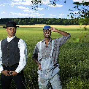 Mustat miehet seisovat viljapellon laidalla, Musta Barbaari pohjalaisasussa ja Prinssi Jusuf maanviljelijän haalareissa