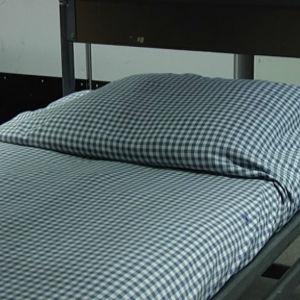 Bäddad säng i arméstuga.
