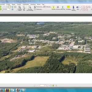 Ett flygfoto över ett planerat industriområde. Skog och byggnader, åkrar.