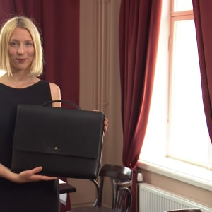 Ida Jonsson håller upp sin egen designade svarta portfölj.