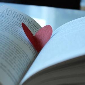 En öppen bok med ett rött pappershjärta mellan sidorna.