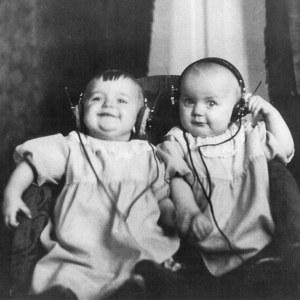 Kaksostyttövauvat kuuntelevat radiota kuulokkeilla 1920-luvun puolivälissä.