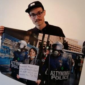Erik Åhman håller upp en av sina bilder från Grekland. Bilden visar en demonstrerande kvinna omgiven av poliser.