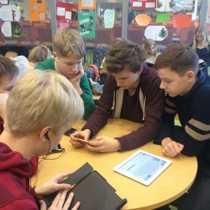 Pojkar sitter runt ett bord och tittar på pekplattor och smarttelefoner.
