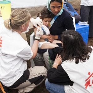 Egima från Afganistan låter sin dotter Satayesh vaccineras i flyktinglägret i Idomeni.