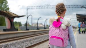 Tyttö reppu selässä asemalaiturilla.