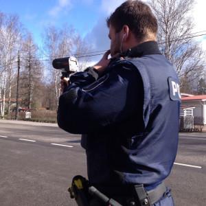 Polisman som kollar hastigheten på kommande bilar.
