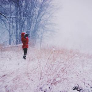 Kvinna som står med röd vinterjacka på sig på en äng.