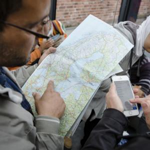 Asylsökande tittar på en karta över Sverige.