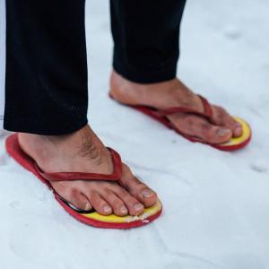 Fötter i flipflops i snö