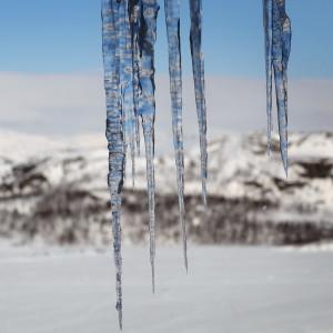 Istappar i förgrunden, snötäckta fjäll i bakgrunden.
