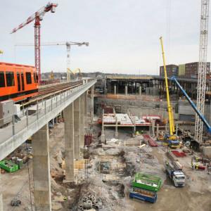 En orangefärgad metro kör förbi byggplatsen med lyftkranar vid Fiskehamnen i Helsingfors.